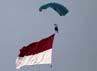 Seorang prajurit TNI melakukan atraksi terjun payung sambil mengibarkan bendera merah putih.