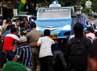 Replika taksi Blue Bird yang mengusung berbagai jenis makanan dikerebuti oleh warga. Mereka mengambil makanan yang ada di replika taksi tersebut.
