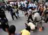 Warga berebutan mengambil makanan yang terjatuh di jalan.