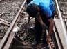 Dua orang pekerja melakukan penambalan balas atau batuan kerikil pada bantalan rel kereta api.