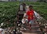 Seorang anak bermain di sekitar Waduk Riario.