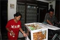 Sepasang Suami -istri sedang menyiapkan berbagai jenis makanan untuk di bawa ke pasar atau ke pabrik-pabrik di wilayah Surabaya