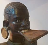 Patung wanita dengan piring di bibir dan telinga (thisbelongsinamuseum.tumblr.com)