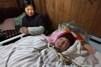 Mesin tersebut terhubung dengan tubuh Xuepeng, yang tergeletak di tempat tidur dengan mengenakan topi merah untuk melindunginya dari serangan dingin. (Foto: AFP)