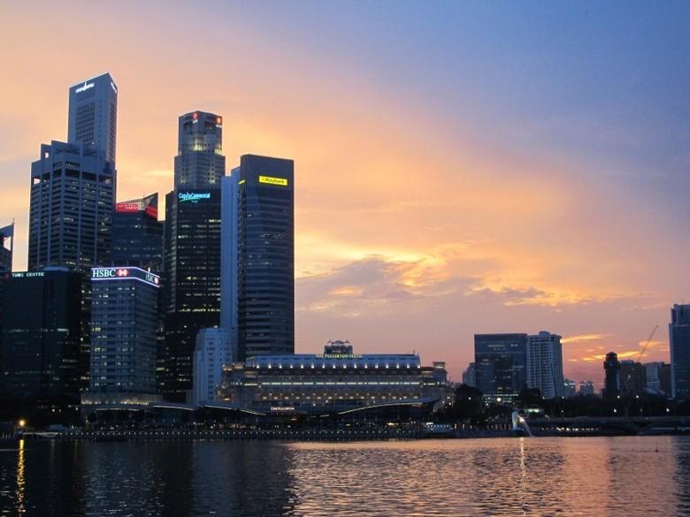 Langit senja berwarna kuning keemasan dan kerlap-kerlip lampu gedung yang terlihat dari pelataran Marina Bay (Afif/detikTravel)