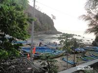 Aktivitas nelayan di pinggiran pantai dengan perahu biru kebanggan mereka.