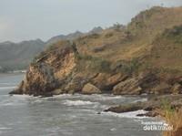 Pemandangan perbukitan dengan terjangan ombak yang menghempas tebing-tebingnya.