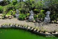 Taman dengan kolam ikan dan patung dewa-dewa