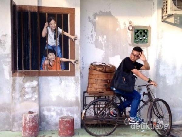 Ketika berada di Penang, Malaysia, wisatawan bisa menikmati aneka street art yang menggabung mural dengan instalasi benda seni. Misalnya saja sepeda yang kita naiki dengan lukisan anak-anak di dinding. Keren!