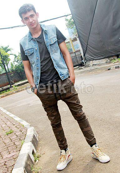 Ia memadukan celana army-nya dengan kaus hitam, rompi denim dan sepatu putih. Pool/Gus Mun/detikFoto.
