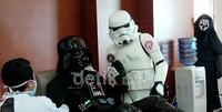 Stormtrooper memegang tangan Darth Vader yang sedang donor darah, sementara Darth Nihilius hanya mengintip dari kejauhan.