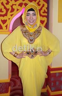 Bella tampil dibalut hijab dan kaftan serba kuning.
