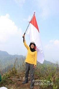 seorang pendaki mengibarkan merah-putih di puncak Aseupan