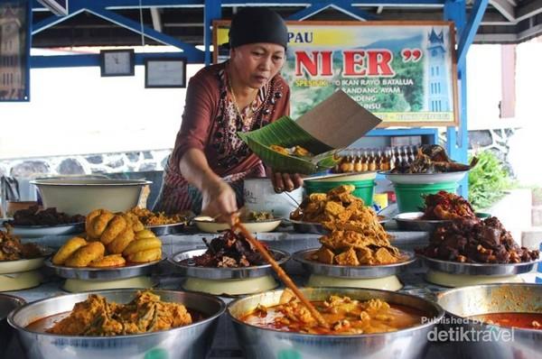 Seorang penjual Nasi Kapau sedang mengambil lauk pauk