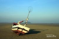 Perahu nelayan di tepi pantai yang sedang surut