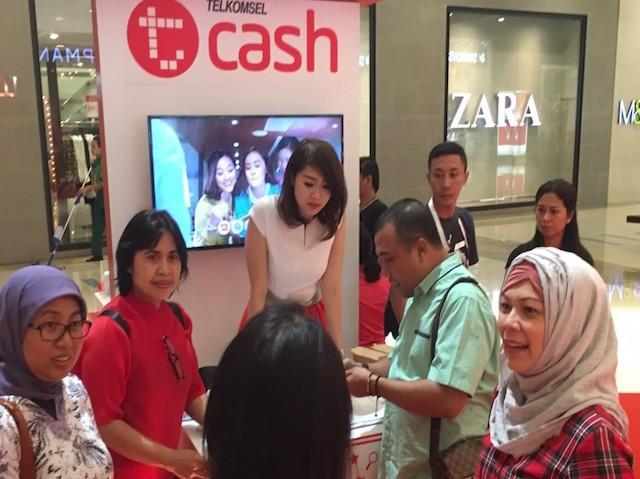 EVP Area Jabotabek Jabar Telkomsel, Venusia Papasi (kedua dari kiri), saat menjelaskan layanan TCash Tap kepada salah satu pelanggan di Booth TelkomselFest Jakarta. Ajang Festival Digital ini untuk mengenalkan layanan Digital Lifestyle kepada masyarakat.