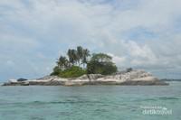 Pulau kecil berbatu dan sedikit pohon kelapa tidak jauh dari Pulau Lengkuas.