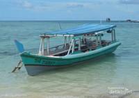 Sebuah perahu sedang bersandar di Pantai Pulau Kepayang, dengan airnya yang sangat jernih.