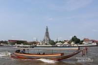 Sebuah kapal melintas dengan latar Wat Arun