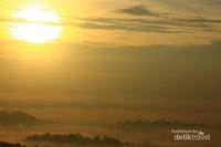 Matahari dengan megahnya di antara goresan awan yang menimbulkan warna yang dramatis