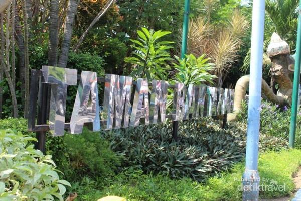 Papan nama yang terletak di depan taman