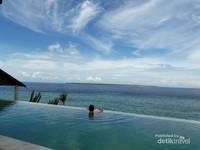 Infinity pool menghadap laut sambil dengan suasana khas Tanjung Bira nan tenang,