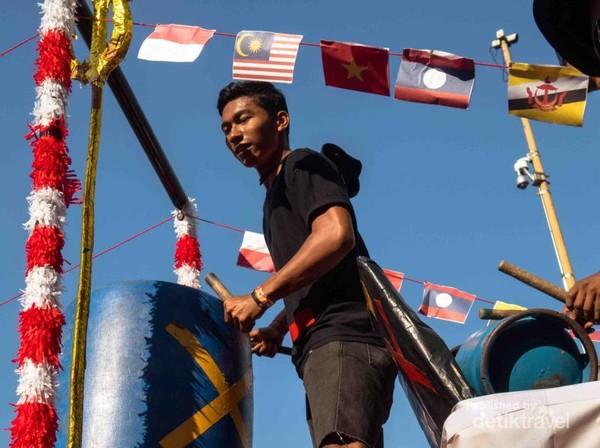 Seniman lokal dengan alat musik sederhana mengiringi deretan bendera anggota ASEAN.