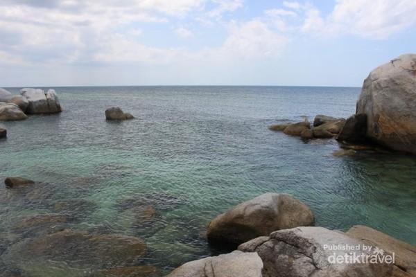 Air yang tenang di sekitar pulau dengan batu-batu di dasarnya terlihat jelas dari kejauhan.