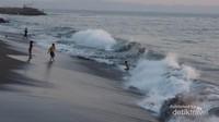 Ombak yang besar tak menyurutkan pengunjung untuk sekedar bermain air di bibir pantai