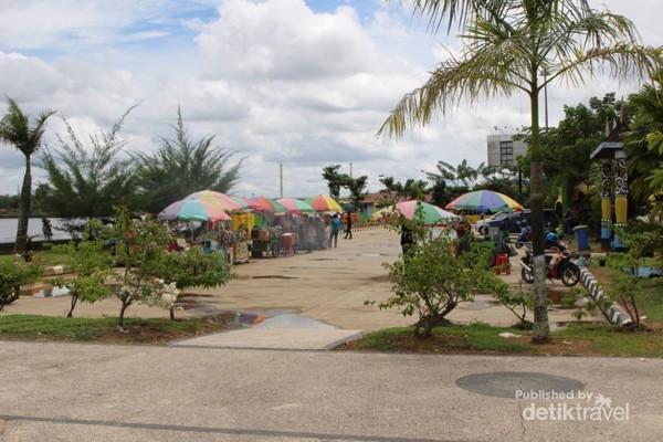 Pedagang makanan dan minuman dengan tenda warna-warni yang ada di taman.