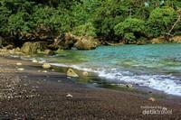 Pantai Anoi Itam. Kilauan pasir hitamnya yang disapu air laut membuatnya berkilau eksotis.