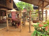 Para wanita yang menenun kain di depan rumahnya