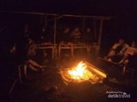 Berkumpul di api unggun di tepi pantai.