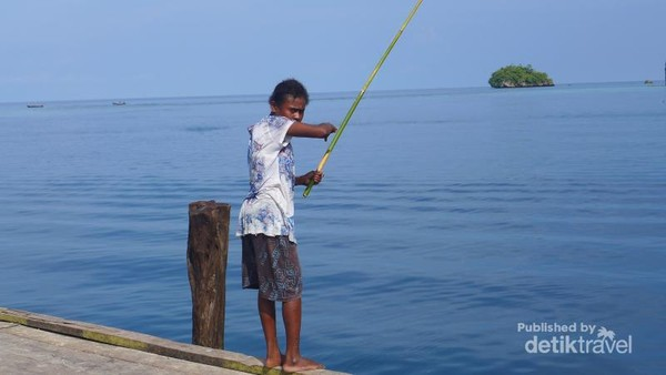Seorang anak yang sedang memancing dengan bilah bambu