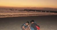Anak-anak bermain pasir di pantai menikmati suasana