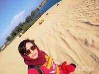 Penulis dengan latar belakang danau dan kendaraan ATV yang digunakan untuk berkeliling di hamparan pasir putih di9 White Sand Dunes, Mui Ne