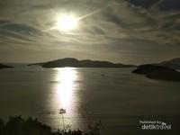 Hiasan perbukitan berpadu dengan pulau kecil yang indah saat sunset.