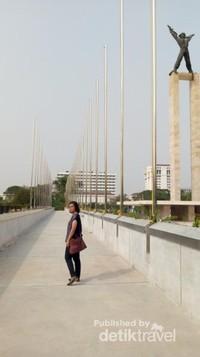 Berfoto dengan latar belakang tiang-tiang bendera dan monumen