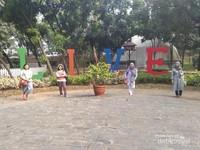 Pengunjung berswafoto dengan icon LIVE di Taman Cikokol