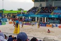 Pasangan atlet bola voli pantai putri Indonesia sedang berlaga.