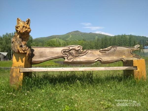 Kursi dengan hiasan serigala berlatar pegunungan nan indah