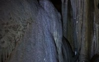 Nah ini foto batuan kristal dari jarak dekat . Tampak titik titik putih kristal menempel pada bebatuan yang berkilauan dalam gelap .