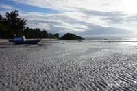 Sebuah perahu terlihat di atas pantai yang airnya sedang surut