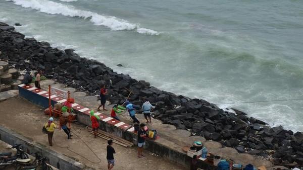 Nelayan sedang menarik perahunya ke pelabuhan