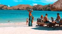 Penjual kain tenun khas Lombok sedang berjualan di Pantai Tanjung Aan