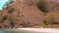 WIsatawan sedang mendaki bukit yanga ada di Pulau Kelor