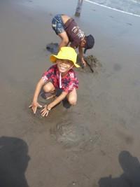 bocah yang bahagia bermain pasir di pantai
