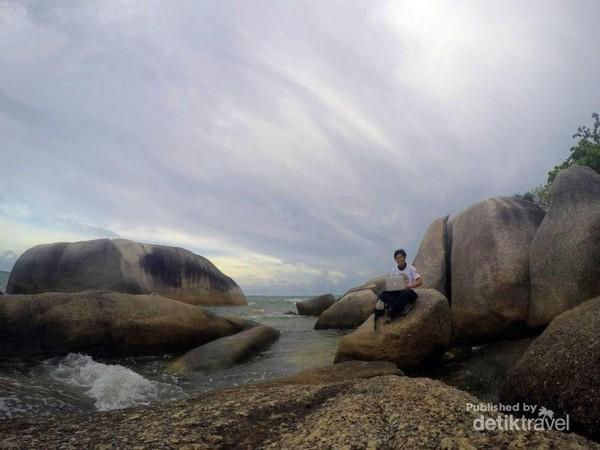 Menikmati sore di pantai tanjung tinggi sambil duduk diatas batuan yang tinggi