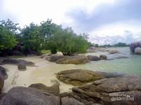 Pemandangan pantai yang dihiasi batuan granit yang banyak