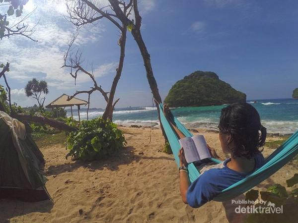 Menikmati suasana pantai sambil menaiki hammockan dan membaca buku